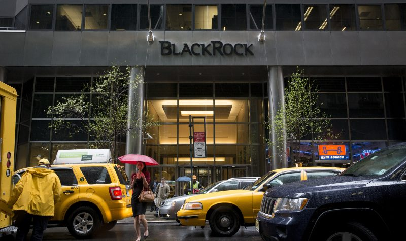 Pedestrians walking with umbrellas pass by taxi in front of BlackRock Inc. offices in New York, U.S., on Friday, April 12, 2013. BlackRock Inc. predicts Canadian 10-year benchmark bond yields may fall to the lowest since at least the 1950s as a sputtering economy douses expectations the Bank of Canada will increase borrowing costs this year. Photographer: Scott Eells/Bloomberg via Getty Images